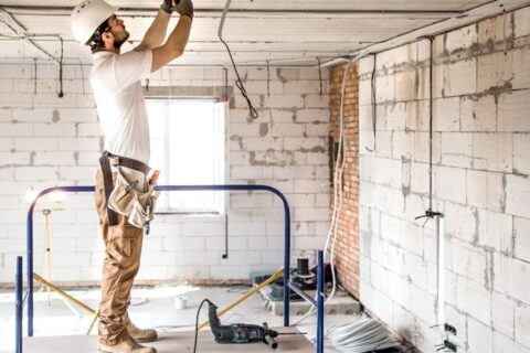 A professional electrician working in a commercial facility