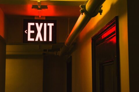 An exit sign illuminated in red color hangs from the ceiling