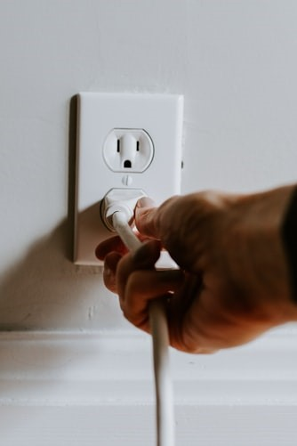 A man plugging in a socket