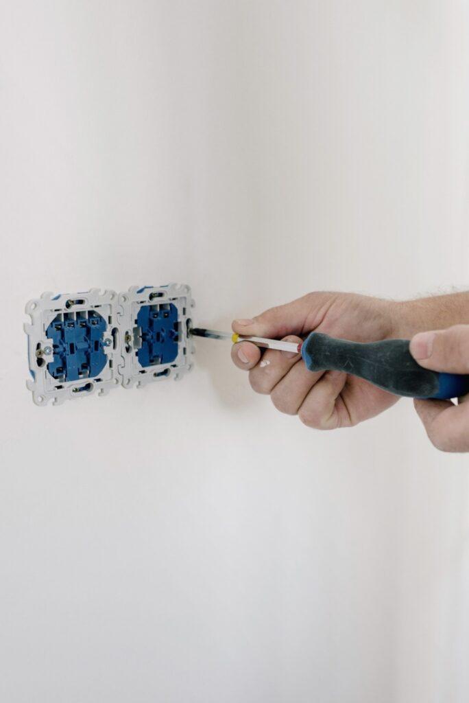 Man-opening-electrical-socket-using-screwdriver